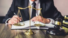 Judge gavel with Justice lawyers, Gavel on wooden table and Counselor or Male lawyer working on a documents at law firm in office. Legal law, advice and stock photo