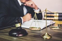 Judge gavel with Justice lawyers, Gavel on wooden table and Counselor or Male lawyer working on a documents at law firm in office. Legal law, advice and royalty free stock images