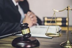 Judge gavel with Justice lawyers, Gavel on wooden table and Counselor or Male lawyer working on a documents. Legal law, advice and. Justice concept stock photo