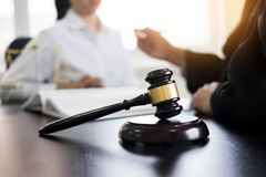 Judge gavel with lawyers advice legal at law firm in background. Royalty Free Stock Image