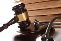 Judge gavel and medical stethoscope. Near law textbook in library archive study room, close-up. Forensic medicine investigation or malpractice justice concept Stock Images
