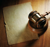 Judge gavel and paper sheet on wooden background. Stock Photos