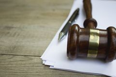 Judge gavel, pen and paper for notes on the wooden table. stock photo