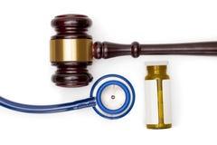 Judge gavel, pills bottle and stethoscope on white backround Stock Photography