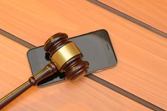 Judge gavel on smartphone, wooden law background Royalty Free Stock Photos