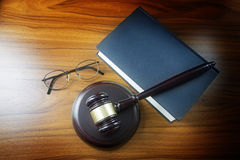 Judge gavel with sound board, blue statute book and glasses on a Royalty Free Stock Image