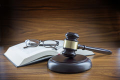 Judge gavel with sound board, book and glasses on a wooden desk, lawyers working place with justice symbol, concept for law and c stock image