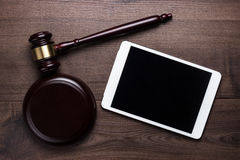 Judge gavel and tablet computer on brown wooden Royalty Free Stock Image