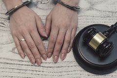 Judge gavel on wooden background with woman hands in handcuffs royalty free stock image