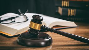 Judge gavel on a wooden desk, law books background Royalty Free Stock Photo