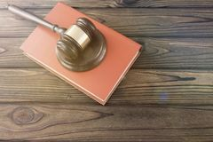 Judge hammer, book on a wooden background. Hammer judge lies on the book collection of legal acts on the background of wooden table stock images