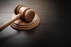 Judge hammer on brown lacquered wooden desk Royalty Free Stock Photography