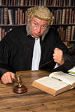 Judge with hammer. Mature judge with authentic court wig holding a gavel in court royalty free stock images