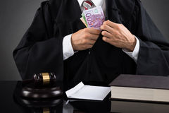 Judge Hiding Banknote At Desk Royalty Free Stock Photography