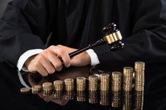 Judge Hitting Gavel In Front Of Coins Royalty Free Stock Photography