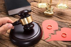 Judge Hitting Mallet By Broken Paper Heart With Rings. And justice scale on wooden table Stock Photography
