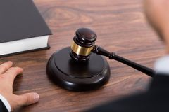 Judge Hitting Mallet At Desk. Close-up Of Judge Hitting Mallet At Wooden Desk In Courtroom Stock Photos