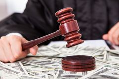 Judge hitting mallet on dollar. Close-up Of Male Judge Hitting Mallet On Banknote Royalty Free Stock Images