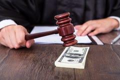 Judge hitting mallet on dollar. Close-up Of Male Judge Hitting Mallet On Banknote Royalty Free Stock Image
