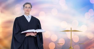 Judge holding book by law scales Royalty Free Stock Image