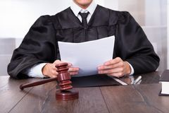 Judge holding documents. Close-up Of Male Judge In Front Of Mallet Holding Documents stock photos