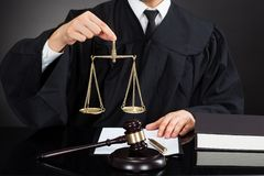 Judge holding weight scale at desk Royalty Free Stock Photos