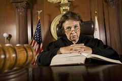 Judge With Law Book. Portrait of female judge with law book in the courtroom Stock Photography