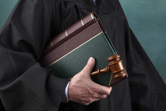 Judge, law book and gavel. Judge in black judicial robes coming from courtroom holding law book and gavel Royalty Free Stock Photography
