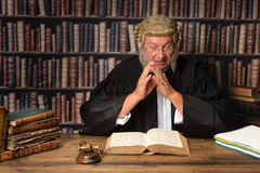 Judge with law books. Mature judge in court consulting law books stock photography