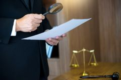 Judge lawyer read paper text by use Magnify glass. Concept law firm Stock Photo