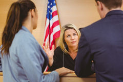 Judge and lawyers speaking in front of the american flag Stock Photos