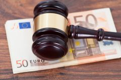 Judge mallet on euro banknotes. Closeup of judge mallet over euro banknotes on table royalty free stock photos