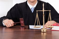 Judge with mallet and weight scale in courtroom. Midsection of male judge with mallet and weight scale at table in courtroom Stock Photography