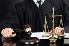 Judge with mallet and weight scale at desk Stock Images