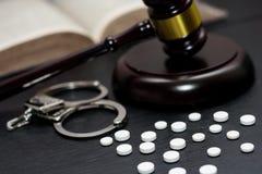 Judge& x27; mazo de s con las esposas, drogas en la tabla de madera imagen de archivo