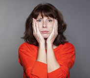 Judge mental concept for resigned beautiful 50s woman. Judge mental concept - resigned beautiful 50s woman expressing despair and disillusion with hand gesture Stock Image