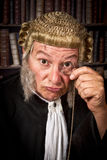 Judge with monocle. Vintage judge looking through a monocle in court stock images