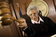 Judge Pointing Gavel In Courtroom. Senior female judge pointing gavel in courtroom stock photos