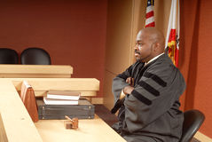 Judge presiding over trial. African American judge sitting in his courtroom while presiding over trial Stock Photos