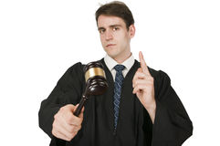 Judge raising the index finger on white. Upper view of a young man in judicial robes against white background with a gavel in his right hand, seriously and with royalty free stock photo