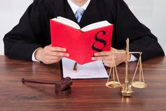 Judge reading book at table in courtroom Stock Photos