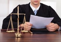 Judge reading document at table in courtroom. Midsection of male judge reading document at table in courtroom Royalty Free Stock Photos