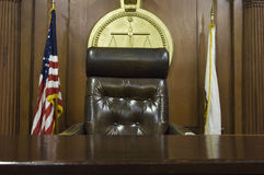 Judge's Chair In Court. Judge's chair and flags in courtroom royalty free stock photos