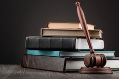 Judge`s gavel and books. Judge`s gavel and heap of books on dark background. Legal knowledge and juridical system concept royalty free stock photo