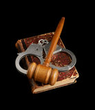 Judge's gavel and handcuffs on old legal book Stock Image