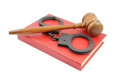 Judge's gavel and handcuffs on red book Royalty Free Stock Photography