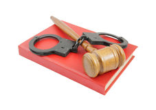 Judge's gavel and handcuffs on red book Royalty Free Stock Photos