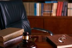 Judge`s Gavel or mallet on wooden table. With law books and eyeglasses, library background. Courtroom theme close-up. Education and legal law concept Royalty Free Stock Photo