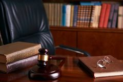 Judge`s Gavel or mallet on wooden table. With law books and eyeglasses, library background. Courtroom theme close-up. Education and legal law concept Stock Photo