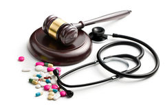 Judge's gavel with stethoscope and pills Royalty Free Stock Photos